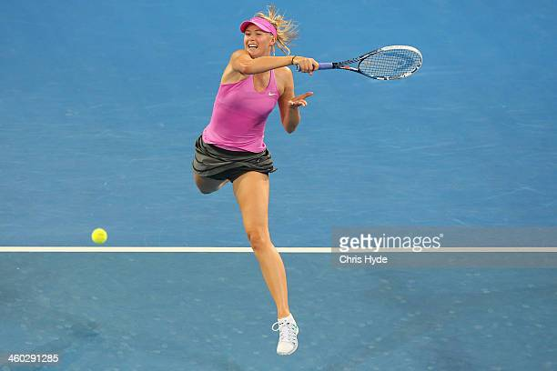 Maria Sharapova of Russia plays a forehand in her match against Serena Williams of the USA during day six of the 2014 Brisbane International at...