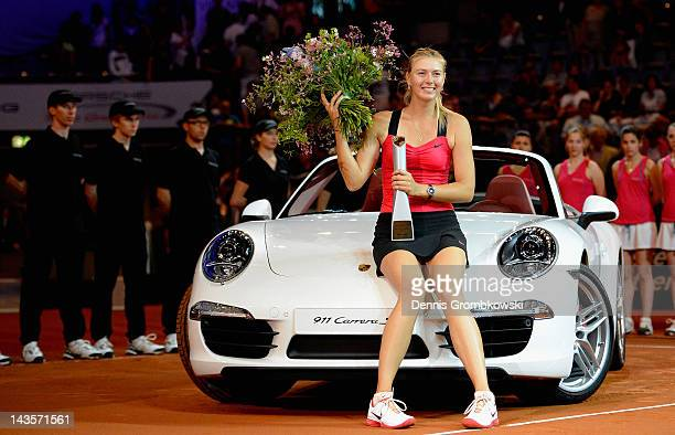 Maria Sharapova of Russia poses with her new Porsche Carrera 911 GTS after winning her final match against Victoria Azarenka of Belarus during day...