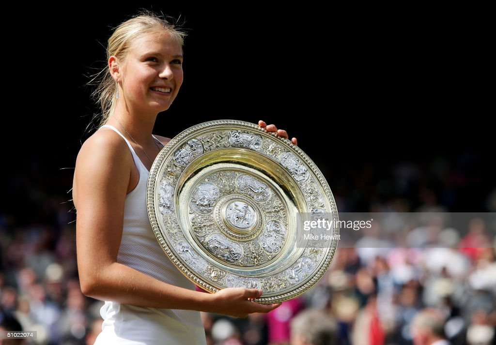 Maria Sharapova of Russia poses with her trophy after she won against Serena Williams of USA in the ladies final match at the Wimbledon Lawn Tennis Championship on July 3, 2004 at the All England Lawn Tennis and Croquet Club in LondonSharapova won 6-1 6-4.