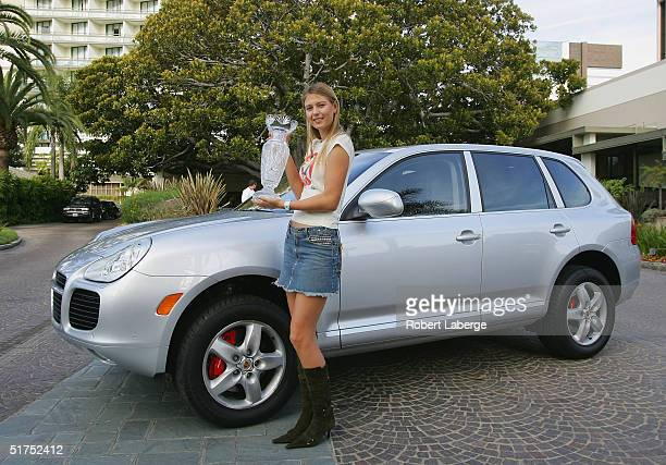 Maria Sharapova of Russia poses with the Billie Jean King Trophy in front of a Porsche Cayenne the day after winning the single's title at the WTA...