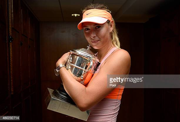 Maria Sharapova of Russia poses with the Coupe Suzanne Lenglen trophy in her changing room following her victory in her women's singles final match...