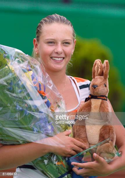 Maria Sharapova of Russia poses with the runner-up trophy and other gifts following her loss to Barbora Strycova of the Czech Republic in the junior...