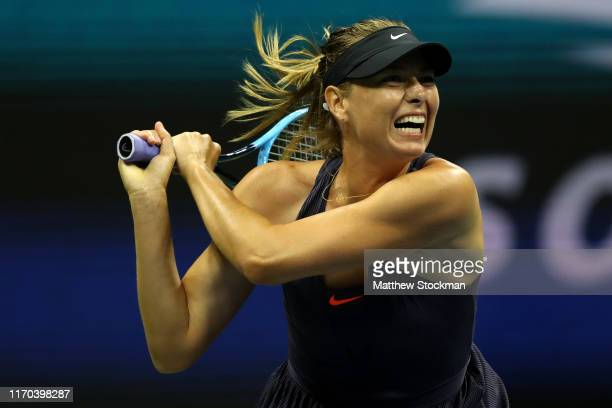 Maria Sharapova of Russia returns a shot during her Women's Singles first round match against Serena Williams of the United States during day one of...