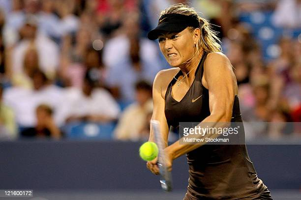 Maria Sharapova of Russia returns a shot to Vera Zvonareva of Russia during the Western & Southern Open at the Lindner Family Tennis Center on August...
