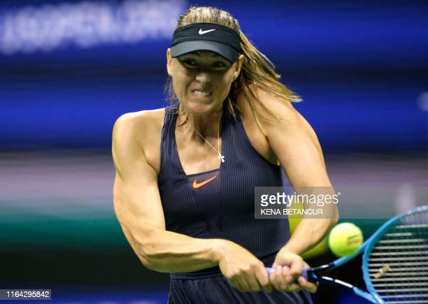 TOPSHOT Maria Sharapova of Russia returns the ball to Serena Williams of the United Sates during their Round 1 women's Singles match at the 2019 US...