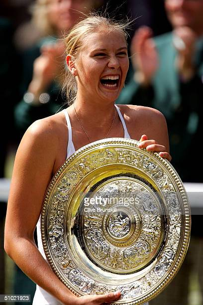 Maria Sharapova of Russia smiles as she holds her trophy after her victory against Serena Williams of USA in the ladies final match at the Wimbledon...