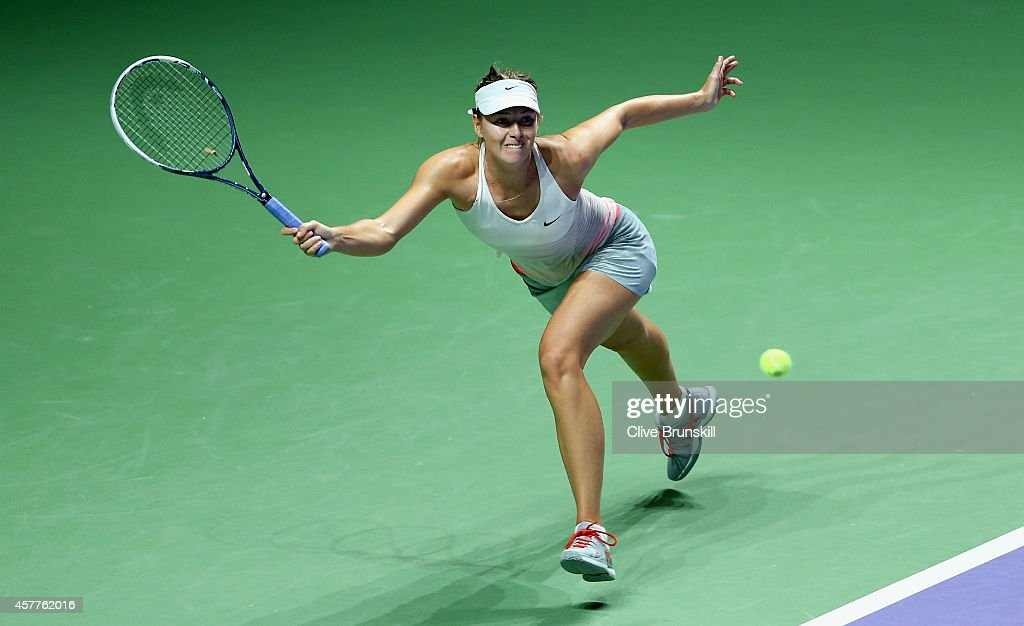 Maria Sharapova of Russia stretches to play a forehand against Agnieszka Radwanska of Poland in their round robin match during the BNP Paribas WTA Finals at Singapore Sports Hub on October 24, 2014 in Singapore.
