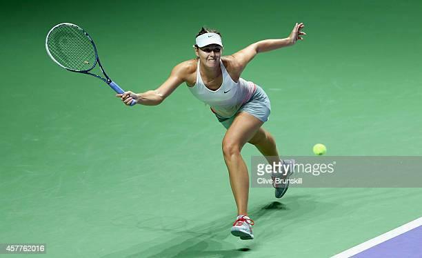 Maria Sharapova of Russia stretches to play a forehand against Agnieszka Radwanska of Poland in their round robin match during the BNP Paribas WTA...