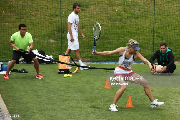 Maria Sharapova of Russia trains during a practice session with members of her coaching team on day two of the Wimbledon Lawn Tennis Championships at...