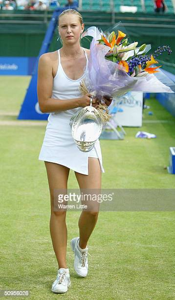 Maria Sharapova of Russia walks off court with the trophy after beating Tatiana Golovin of France to win the DFS Classic Womens International Tennis...