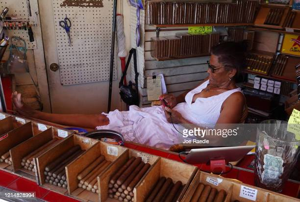 Maria Smith waits for the few customers to stop by her cigar stand as the city government takes steps to fight the coronavirus outbreak on March 25...