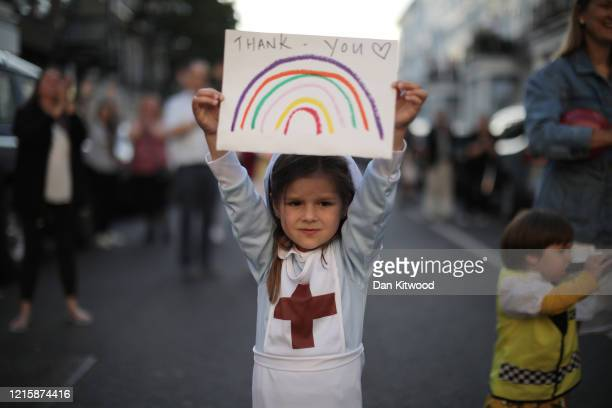 Maria Sole dressed in a small nurses outfit holds up a rainbow drawing with the words 'Thank You' on it as NHS staff and members of the public take...