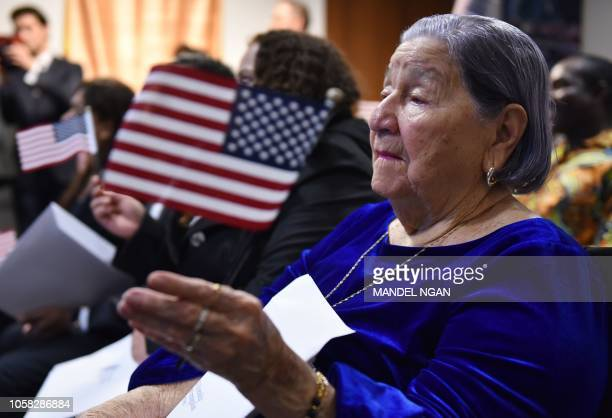 Maria Valles Bonilla waves a US flag during a naturalization