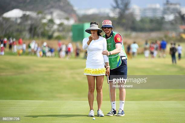 Maria Verchenova of Russia and her caddie line up a putt on the seventh green during the Women's Golf Final on Day 15 of the Rio 2016 Olympic Games...