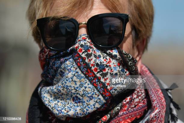 Maria wears a protective scarf while in a street in Krakow From today until further notice the Ministry of Health introduced a new rule that requires...