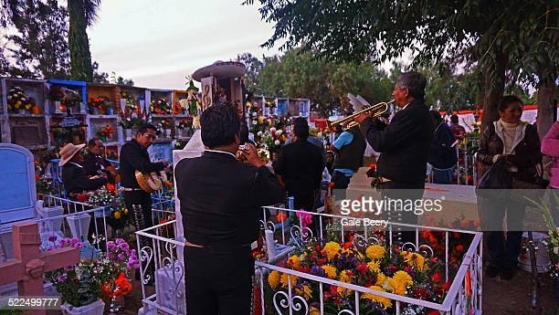 Mariachi band playing Favorite music of the Deceased at the grave in The cemetery at San Miguel de Allende Mexico Day of the Dead All Souls Day...