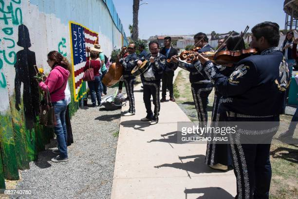 A mariachi band plays as part of Mother's Day celebrations at the MexicoUS border in Playas de Tijuana in northwestern Mexico on May 13 2017 This...