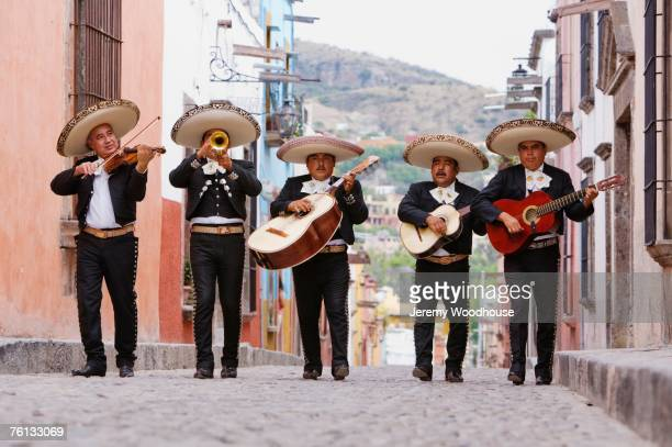 mariachi band walking in street - mexique photos et images de collection
