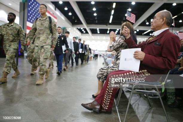 Mariachi musician and new US citizen Cirilo Casillas originally from Mexico holds an American flag as new US citizen military members walk past at a...
