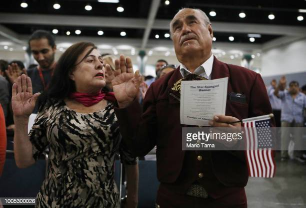 Mariachi musician and new US citizen Cirilo Casillas originally from Mexico raises his hand during a naturalization ceremony on July 25 2018 in Los...