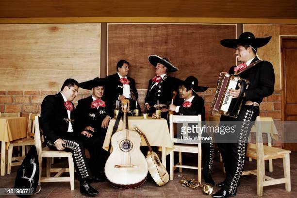 mariachi musicians relaxing together in restaurant - mariachi fotografías e imágenes de stock