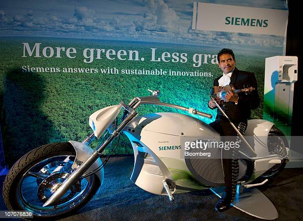 A mariachi player poses on an electric motorcycle powered by Siemens technology in the Siemens Smart Grid Dome in Plaza Santo Domingo in Mexico City...