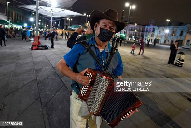 Mariachi wears a face mask as he plays the accordion looking for clients at Garibaldi square in Mexico City, on March 19, 2020 in spite of the new...
