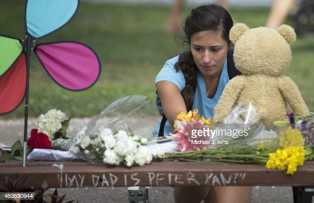 Mariagrazia LaFauci of Waltham, Massachusetts places a teddy bear on a fan memorial in honor of Robin Williams on the bench made famous by his movie...