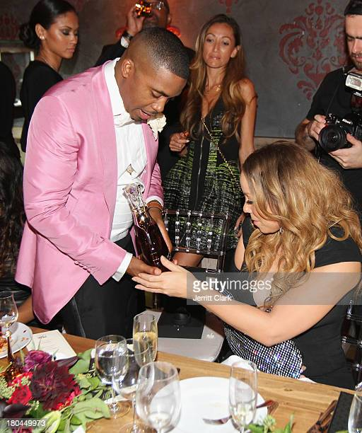 Mariah Carey checks out Nas' bottle of Hennessy Paradis Imperial at Nas 40th Birthday Celebration Dinner And Party at Avenue NYC on September 12,...