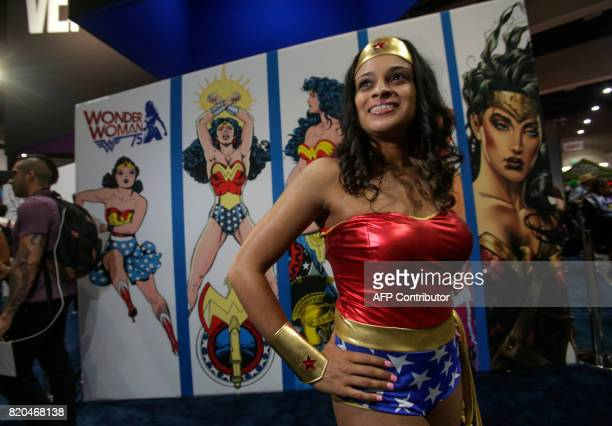 Mariah Cletus plays Wonder Woman in front of a poster showing Wonder Womans through the years at ComicCon 2017 in San Diego California July 21 2017 /...