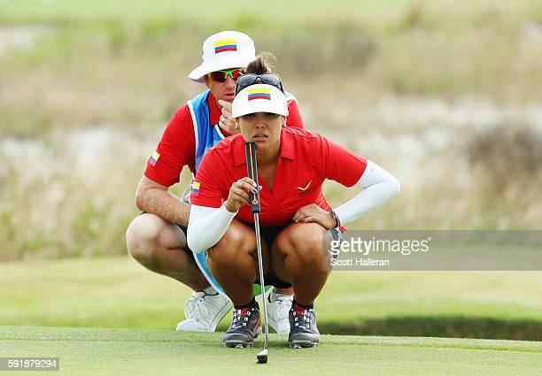 Mariajo Uribe of Colombia waits with her caddie Shane Codd on the 17th green during the second round of the Women's Individual Stroke Play golf on...