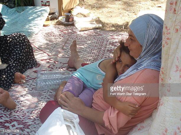 Mariam Mahmoud al Hajj comforts her daughter, Amal, in a Beirut park where she and her family have lived for three weeks. The families three bedroom...