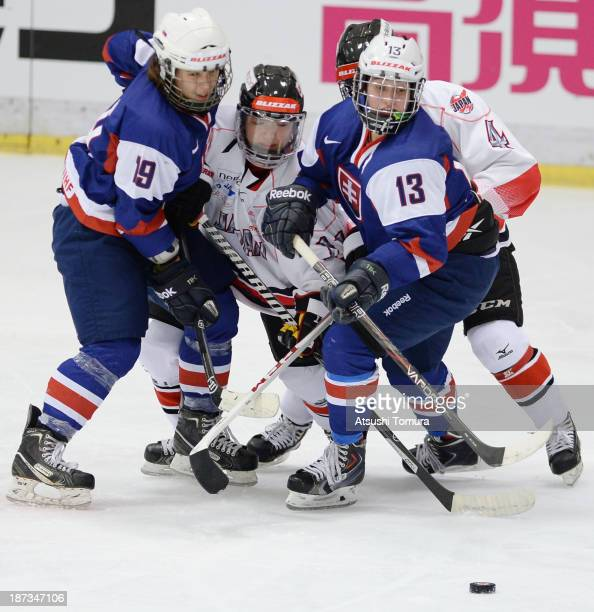 Mariam Mikeskova of Slovakia, Yurie Adachi of Japan, Petra Jurcova of Slovakia and Ayaka Toko of Japan compete for the puck during the match between...