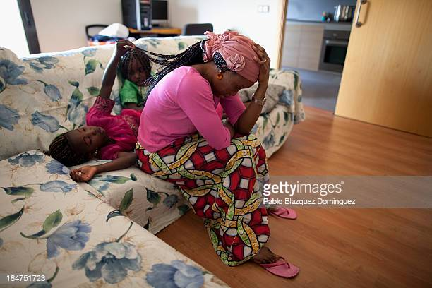 Mariama Siall sits in her sofa with her daughter Kaliatu and a friend in a block of flats occupied by the anti evictions platform on October 15 2013...