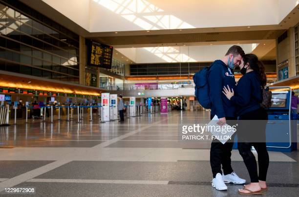Marian Fisher hugs her husband and US Navy sailor Tyler Fisher goodbye as he returns to his duty station overseas after a two week leave together...