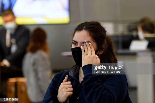 Marian Fisher wipes tears from her eyes after saying goodbye to her husband and US Navy sailor Tyler Fisher as he returns to his duty station...