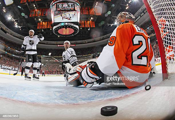 Marian Gaborik and Alec Martinez of the Los Angeles Kings gesture towards goaltender Ray Emery of the Philadelphia Flyers and the loose puck after a...
