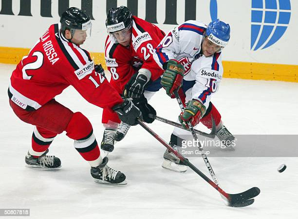 Marian Gaborik of Slovakia fights for the puck with Patric Della Rossa and Martin Pluss of Switzerland in the teams' quarter finals match at the...