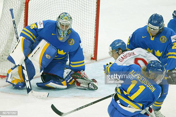 Marian Gaborik of Slovakia gets slowed down by Daniel Alfredsson, Per-Johan Axelsson and goalie Henrik Lunqvist of Sweden in the teams' Group F...