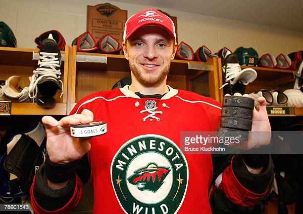Marian Gaborik of the Minnesota Wild holds the puck from his fifth goal as well as four other pucks representing his other goals scored in the game...