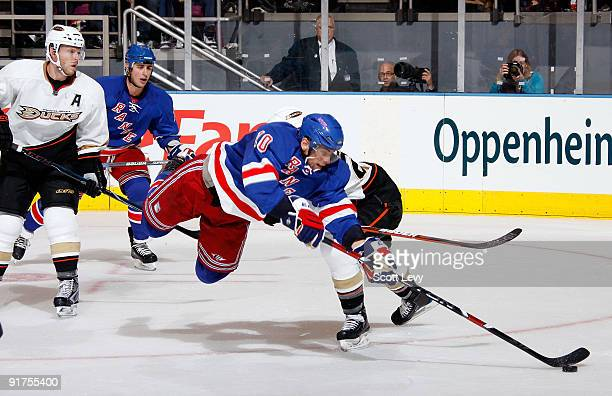 Marian Gaborik of the New York Rangers flies through the air in pursuit of the puck against Scott Niedermayer of the Anaheim Ducks on October 11 2009...