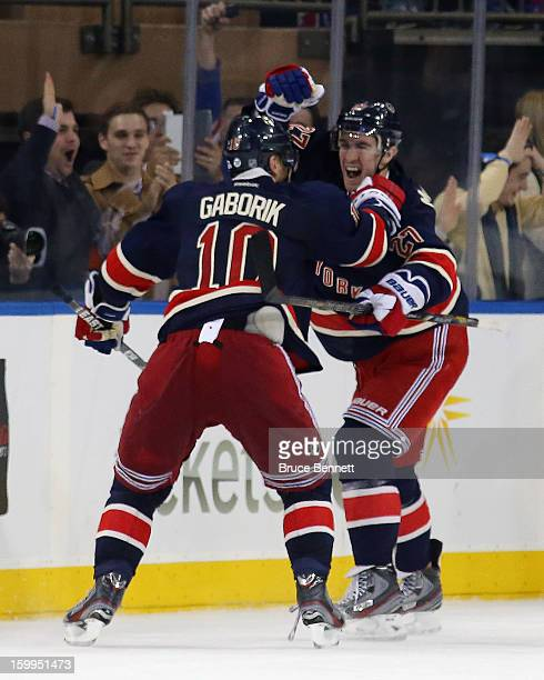 Marian Gaborik of the New York Rangers scores his third goal of the game in overtime to defeat the Boston Bruins, and is joined by Ryan McDonagh at...