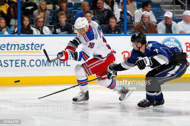 Marian Gaborik of the New York Rangers shoots the puck against Brett Clark of the Tampa Bay Lightning in the second period at the St Pete Times Forum...