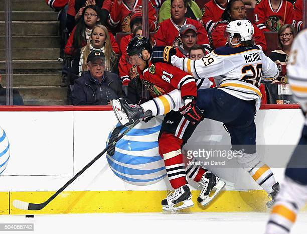Marian Hossa of the Chicago Blackhawks and Jake McCabe of the Buffalo Sabres battle against the boards at the United Center on January 8 2016 in...