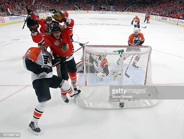 Marian Hossa of the Chicago Blackhawks celerbrates after scoring a goal past Michael Leighton and Lukas Krajicek of the Philadelphia Flyers in the...