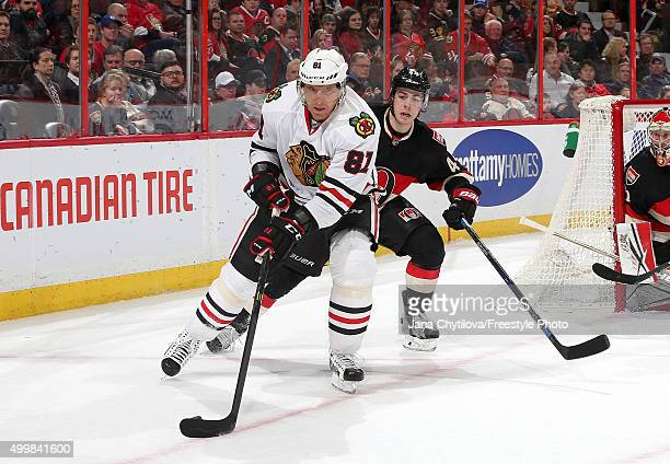 Marian Hossa of the Chicago Blackhawks controls the puck against JeanGabriel Pageau of the Ottawa Senators during an NHL game at Canadian Tire Centre...