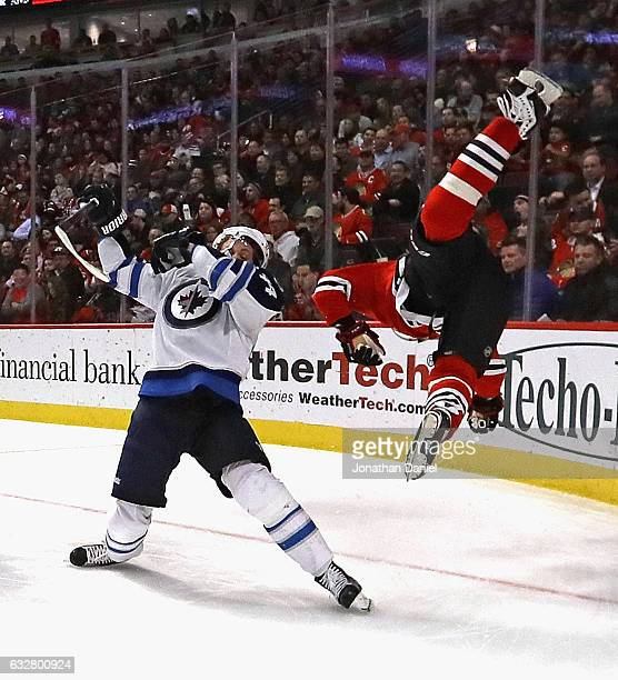 Marian Hossa of the Chicago Blackhawks flips through the air after colliding with Josh Morrissey of the Winnipeg Jets at the United Center on January...