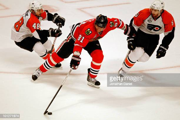 Marian Hossa of the Chicago Blackhawks handles the puck against Braydon Coburn and Danny Briere of the Philadelphia Flyers in Game One of the 2010...