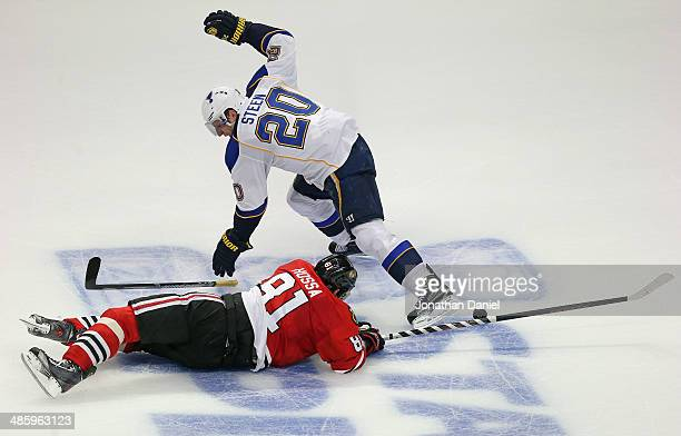 Marian Hossa of the Chicago Blackhawks hits the ice after being hooked by Alexander Steen of the St. Louis Blues in Game Three of the First Round of...