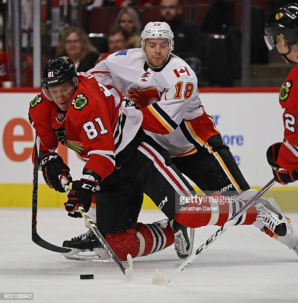 Marian Hossa of the Chicago Blackhawks is knocked to the ice by Matt Stajan of the Calgary Flames at the United Center on November 1 2016 in Chicago...